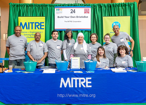 Some of the MITRE employees and family members who volunteered at the event (left to right): Demetrius Davis, Shiva Anand, Kenan Unal, Lynette Wilcox, Salwa Abdul-Rauf, Dahuong Phan, Andrea Ton (seated), Katie Murray, Jon Cline, and Samm Geyer (seated).